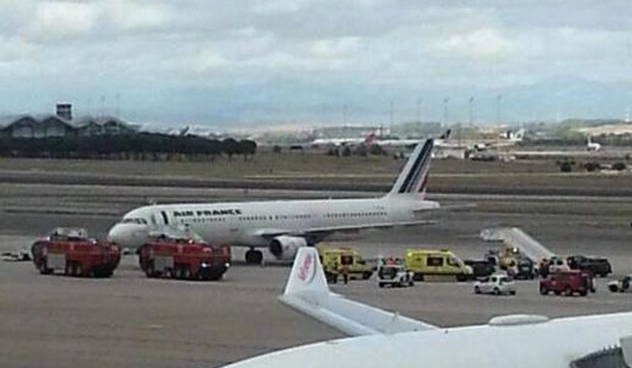 Emergency crews stand next to a plane, carrying 163 people, at the Madrid Airport, Spain, Thursday, Oct. 16, 2014. An Air France plane was isolated at Madrid's airport on Thursday because of a suspected Ebola case after a passenger was reported to have a fever and shivers, officials said. The passenger, who had traveled from Lagos, Nigeria, was taken by ambulance to an unspecified hospital in Madrid but the rest of the passengers were allowed to leave the plane as normal, Air France said in a statement. (AP Photo/Antoni Manchado)