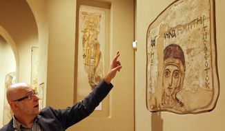 A man points at a 9th century wall painting of Saint Anna in an enhanced exhibition of Christian-era paintings from Faras, Sudan, at the National Museum in Warsaw, Poland, on Thursday, Oct. 16, 2014. Polish archaeologists found and saved the paintings in the 1960s in a UNESCO action before they could be flooded by the New Aswan Dam reservoir. Some of the found paintings were brought to the National Museum in Warsaw, the others are in Khartoum, Sudan. (AP Photo/Czarek Sokolowski)