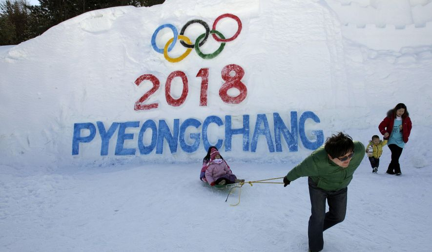 In this Feb. 19, 2011 photo, visitors play with a sled in front of the sign for Pyeongchang 2018 Winter Olympic in Pyeongchang, east of Seoul, South Korea. Pyeongchang organizers have scrapped plans to stage the opening and closing ceremonies for the 2018 Winter Olympic outside of the host city. (AP Photo/Lee Jin-man)