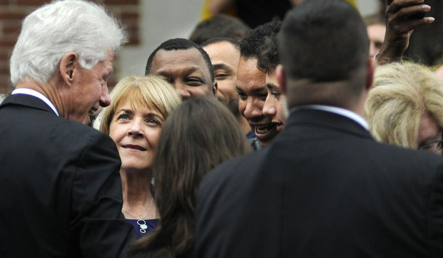 Democratic gubernatorial candidate Martha Coakley, second from left, looks up at former President Bill Clinton, left as he interacts with supporters at a rally event for Coakley and her running mate for lieutenant governor Steve Kerrigan, Thursday, Oct. 16, 2014, at Clark University's Atwood Hall in Worcester, Mass. (AP Photo/Worcester Telegram & Gazette, Christine Peterson)