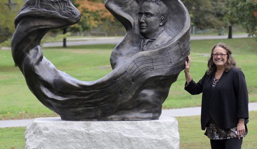 "Sculptor Teresa Clark stands by her bronze work ""A Song For Indiana"" that was dedicated Wednesday, Oct. 15, 2014 in Terre Haute Ind. The sculpture features a relief of Terre Haute native Paul Dresser along with lines of music and some words from his song. Words in  """"On the Banks of the Wabash (Far Away)"" the Indiana state song, are also reflected in some of the artwork worked into the piece. (AP Photo/Tribune-Star, Jim Avelis)"