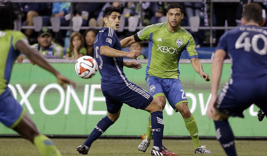 Seattle Sounders' Lamar Neagle, right, passes as Vancouver Whitecaps' Steven Beitashour defends in the first half of an MLS soccer game Friday, Oct. 10, 2014, in Seattle. The Whitecaps won 1-0. (AP Photo/Elaine Thompson)