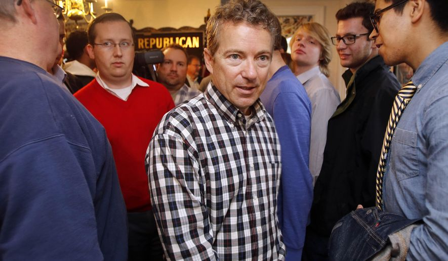 Sen. Rand Paul, R-Ky., walks through a crowd of young Republicans at the state GOP party headquarters Thursday Oct. 16, 2014, in Concord, N.H. The possible 2016 Republican presidential candidate was in the nation's first presidential primary state to rally voters ahead of the November election.(AP Photo/Jim Cole)