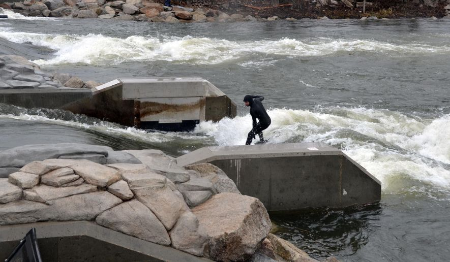 ADVANCE FOR WEEKEND EDITIONS, OCT. 18-19 - This March 31, 2014, photo, a dedicated wakeboard surfer braves the cold spring water to ride the man made rapids at the Boise River Park in Boise, Idaho. (AP Photo/The Idaho Statesman, Roger Phillips)  LOCAL TELEVISION OUT (KTVB 7); MANDATORY CREDIT