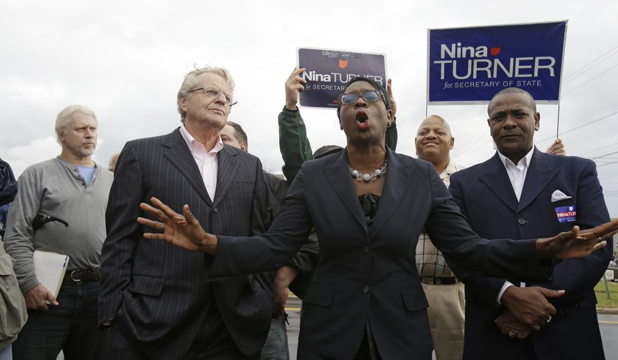 "Jerry Springer listens to state Sen. Nina Turner, center, the Democratic candidate for Ohio's secretary of state, at an early vote event Thursday, Oct. 16, 2014, in Warren, Ohio. Springer, the former Cincinnati mayor and once named ""Democrat of the Year"" in Ohio, remains politically active in the swing state where he previously aspired to be governor. (AP Photo/Tony Dejak)"