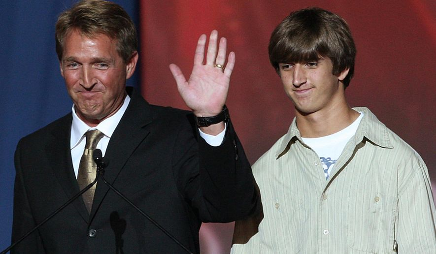 FILE - In this Nov. 4, 2008, file photo, U.S. Rep. Jeff Flake, R-Ariz., appears next to his son Austin at an election night rally in Phoenix. U.S. Sen. Jeff Flake's son Austin is one of four people indicted on cruelty to animal charges after 21 dogs died at a Gilbert, Ariz., kennel in June, prosecutors said Wednesday, Oct. 15, 2014. (AP Photo/Ross D. Franklin, File)