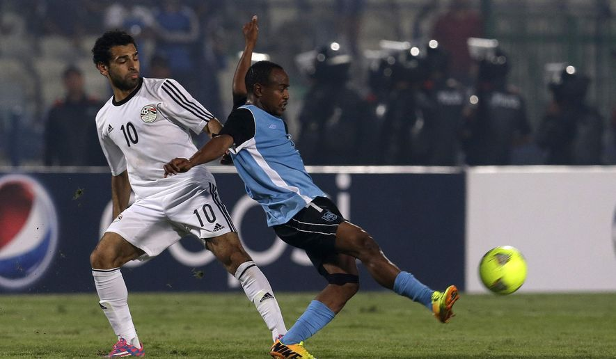 Egypt's Mohamed Salah, left, and Botswana's Thato Ogopotse compete for the ball during their African Cup of Nations group G qualifying soccer match at  Cairo International Stadium in Cairo, Egypt, Wednesday, Oct. 15, 2014. (AP Photo/Hassan Ammar)