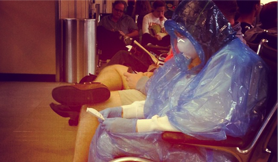 "A photo of a traveler in a homemade ""hazmat"" suit at Dulles International Airport outside Washington, D.C., is making the internet rounds as hundreds of real suits are selling out online. (Twitter/Hall Carter)"