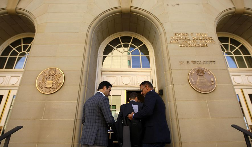 Erik Olvera, left, and Alberto Lammers prepare to enter the Ewing T. Kerr Federal Building on Thursday morning, Oct. 16, 2014, in Casper, Wyo. The two are with the National Center for Lesbian Rights, which is co-council on a lawsuit challenging Wyoming's law that prohibits same-sex marriage. The case was set to be heard Thursday morning by U.S. District Court Judge Scott Skavdahl. (AP Photo/Casper Star-Tribune, Dan Cepeda) MANDATORY CREDIT