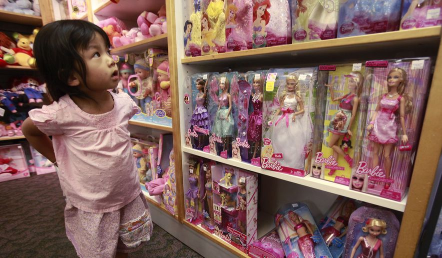 FILE - In this July 14, 2010 file photo, Avi Yisrael, 3, looks at Barbie Dolls, which are produced by Mattel, at a toy store in Palo Alto, Calif. Mattel on Thursday, Oct. 16, 2014 reported that Barbie sales fell 21 percent for the three months ended Sept. 30, 2014, even sharper than the 15 percent drop in the second quarter. (AP Photo/Paul Sakuma, File) **FILE**