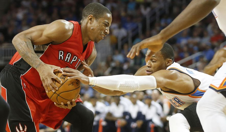 Toronto Raptors'  DeMar DeRozan tries to keep Oklahoma City Thunder's Russell Westbrook from stealing the ball during the first half of a preseason NBA basketball game Friday, Oct. 17, 2014, in Wichita, Kan. (AP Photo/The Wichita Eagle, Jaime Green)