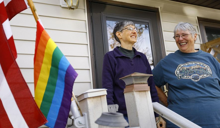 Donna West, left, and Paula McDaniel stand on their porch after putting out their rainbow flag upon hearing the news that a state law banning same-sex marriage was struck down by U.S. District Judge Scott W. Skavdahl on Friday, Oct. 17, 2014, in Casper, Wyo. West and McDaniel have been together almost 19 years. They married in San Diego last year, but their marriage wasn't recognized by the state of Wyoming.  (AP Photo/The Casper Star-Tribune, Dan Cepeda) MANDATORY CREDIT