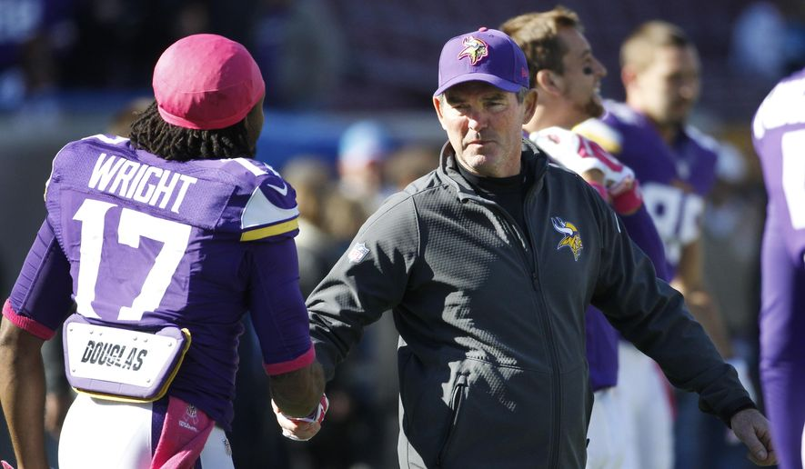 ADVANCE FOR WEEKEND EDITIONS, OCT. 18-19 - FILE -  In this Oct. 12, 2014, file photo, Minnesota Vikings head coach Mike Zimmer shakes hands with wide receiver Jarius Wright before an NFL football game against the Detroit Lions in Minneapolis. Zimmer, in his first season as a head coach after 20 years as an assistant in the NFL, has been learning a lot about the job during a rough start with the Vikings. (AP Photo/Ann Heisenfelt, File)