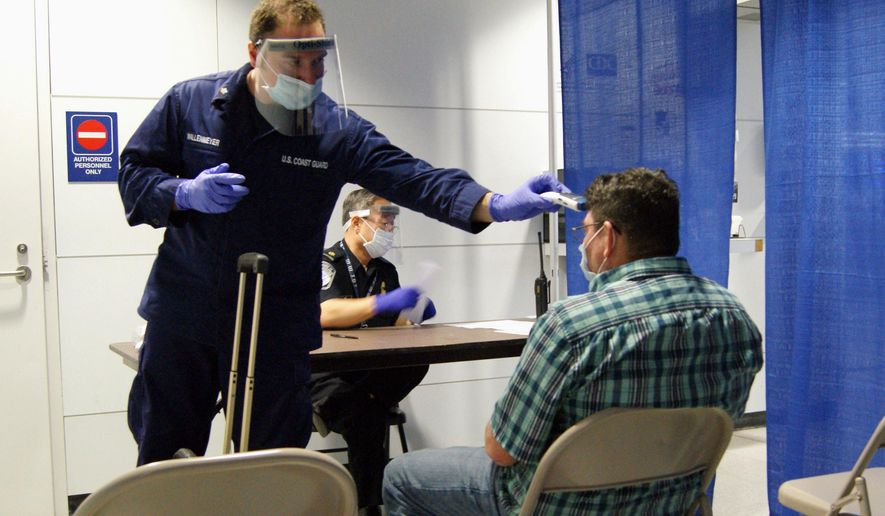 FILE- In this Oct. 16, 2014, file photo, released by U.S. Customs and Border Protection, U.S. Coast Guard Health Technician Nathan Wallenmeyer, left, and CBP supervisor Sam Ko conduct prescreening measures on a passenger, right, who arrived from Sierra Leone at O'Hare International Airport's Terminal 5 in Chicago. Officials recommend against travel to the West African nations of Liberia, Guinea and Sierra Leone, the epicenter of the epidemic. (AP Photo/U.S. Customs and Border Protection, Melissa Maraj, File)