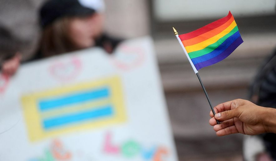 Supporters rally outside of the Federal Building and U.S. Courthouse in Sioux Falls, S.D., Friday, Oct. 17, 2014. A federal judge heard arguments Friday on South Dakota's request to throw out a lawsuit challenging its ban on gay marriage but will file her decision later. (AP Photo/The Argus Leader, Jay Pickthorn)