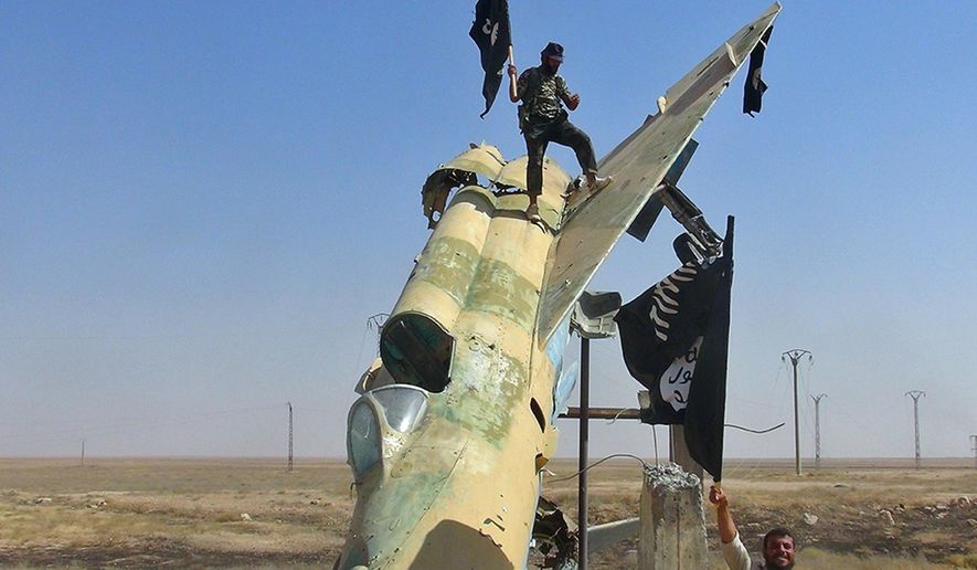 FILE - This undated image posted on Aug. 27, 2014 by the Raqqa Media Center of the Islamic State group, a Syrian opposition group, which has been verified and is consistent with other AP reporting, shows fighters of the Islamic State group waving the group's flag from a damaged display of a government fighter jet following the battle for the Tabqa air base, in Raqqa, Syria.   The Islamic State group is test flying, with the help of former Iraqi air force pilots, several fighter jets captured earlier from air bases belonging to the Syrian military, a Syrian activist group said Friday, Oct. 17, 2014. The report by the Britain-based Syrian Observatory for Human Rights could not be independently confirmed, and U.S. official said they had no reports of Islamic State group militants flying jets in support of their forces on the ground.(AP Photo/ Raqqa Media Center of the Islamic State group)