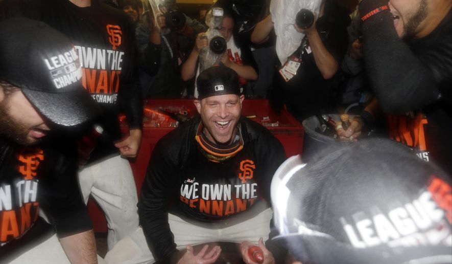 San Francisco Giants' Tim Hudson celebrates in the locker room after Game 5 of the National League baseball championship series against the St. Louis Cardinals Thursday, Oct. 16, 2014, in San Francisco. The Giants won 6-3 to advance to the World Series. (AP Photo/David J. Phillip)