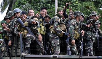 Philippine soldiers react to the media as they head to the mountains to secure the release of two Germans who were held for six months by the Abu Sayyaf militant group, on the volatile island of Jolo, southern Philippines, Friday, Oct. 17, 2014. Philippine Defense Secretary Voltaire Gazmin said the group released Stefan Okonek and Henrike Dielen late Friday on southern Jolo Island. (AP Photo/Nickee Butlangan)