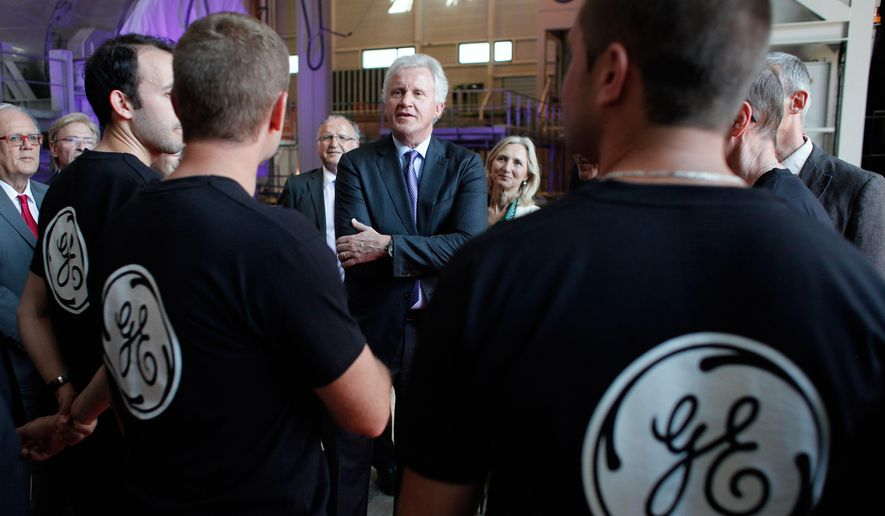 FILE - In this June 24, 2014 file photo, General Electric Co. CEO Jeffrey R. Immelt, center, speaks with workers as he visits the General Electric plant in Belfort, eastern France. General Electric Co. releases quarterly earnings before the market opens on Friday, Oct. 17, 2014. (AP Photo/Thibault Camus, File)