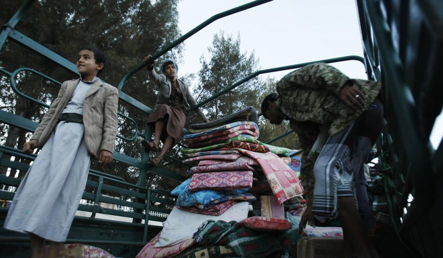 Houthi Shiite rebels collect blankets ahead of remove tents erected two months ago, at a sit-in in a main road leading to the airport in Sanaa, Yemen, Thursday, Oct. 16, 2014. (AP Photo/Hani Mohammed)
