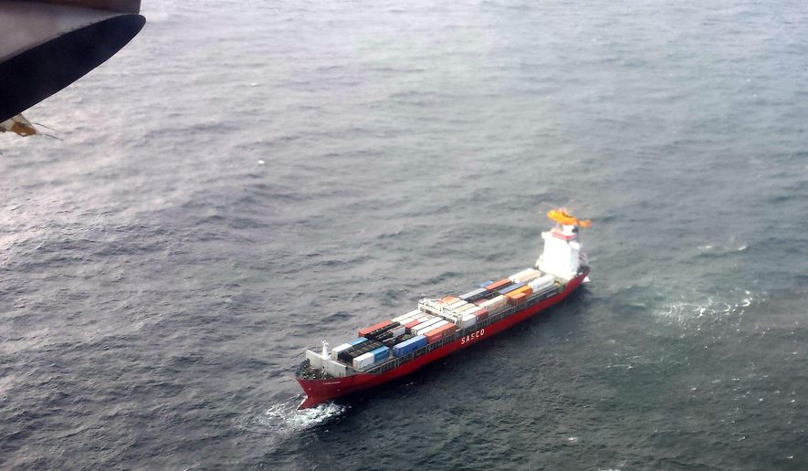 In this aerial photo provided by the Department of National Defense Maritime Forces Pacific, a Canadian Coast Guard helicopter flies near a Russian container ship, carrying hundreds of tons of fuel drifting without power in rough seas off British Columbia's northern coast on Friday, Oct. 17, 2014. The Canadian Forces' joint rescue coordination center in Victoria said the Russian carrier Simushir lost power late Thursday night off Haida Gwaii, also known as the Queen Charlotte Islands, as it was making its way from Washington state to Russia. (AP Photo/The Canadian Press, Department of National Defense Maritime Forces Pacific)