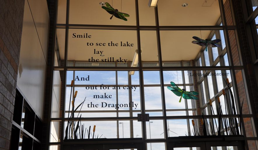 In this Sept. 25, 2014 photo, stained glass dragonflies created by former Fort Atkinson High School students Jourdyn Cluver and Kendra Riddle in their advanced sculpture class hang in the school's lobby behind a poem wall featuring the poetry of the late Fort Atkinson poet Lorine Niedecker in Fort Atkinson, Wis. Former student Caroline Graves did much of the metal work on the metal and stained glass cattails below the dragonflies. (AP Photo/Daily Jefferson County Union, Amy Smith)