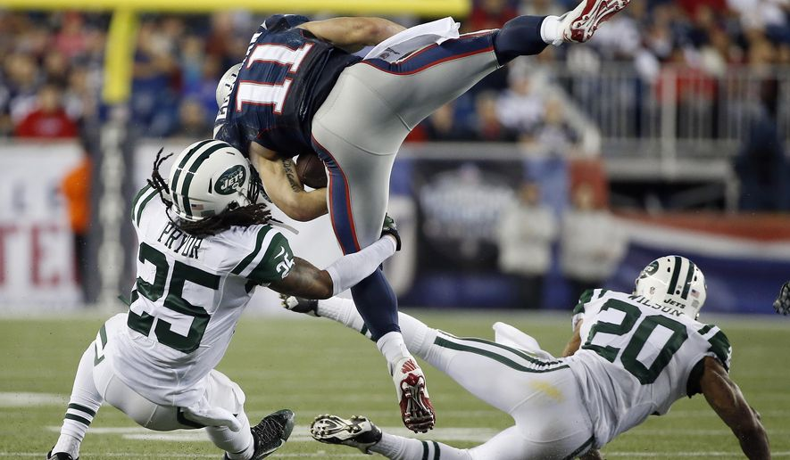 New York Jets defensive backs Calvin Pryor (25) and Kyle Wilson (20) tackle New England Patriots wide receiver Julian Edelman (11) during the second half of an NFL football game Thursday, Oct. 16, 2014, in Foxborough, Mass. (AP Photo/Elise Amendola)