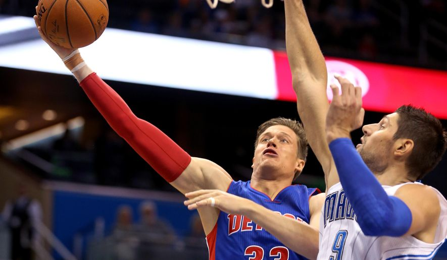 Detroit Pistons forward Jonas Jerebko (33), from Sweden, shoots around Orlando Magic center Nikola Vucevic (9), from Montenegro, during the first half of an NBA basketball preseason game in Orlando, Fla., Friday, Oct. 17, 2014. (AP Photo/Reinhold Matay)