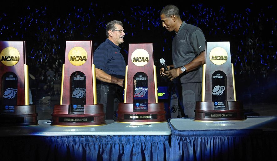 Connecticut women's basketball coach Geno Auriemma, left, and men's basketball coach Kevin Ollie stand with national championship trophies won by the two teams over the years during the NCAA college basketball teams' First Night event, Friday, Oct. 17, 2014, in Storrs, Conn. (AP Photo/Jessica Hill)