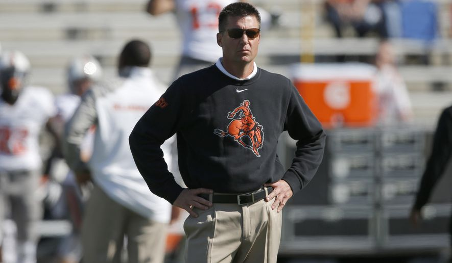 FILE - In this Oct. 11, 2014, file photo, Oklahoma State head coach Mike Gundy watches from the sideline before an NCAA college football game against Kansas in Lawrence, Kan. Gundy wasn't happy with the way his Cowboys played in a lackluster win over Kansas. No. 15 Oklahoma State had better fix their problems soon _ they play at No. 12 TCU on Saturday, Oct. 18. (AP Photo/Orlin Wagner, File)