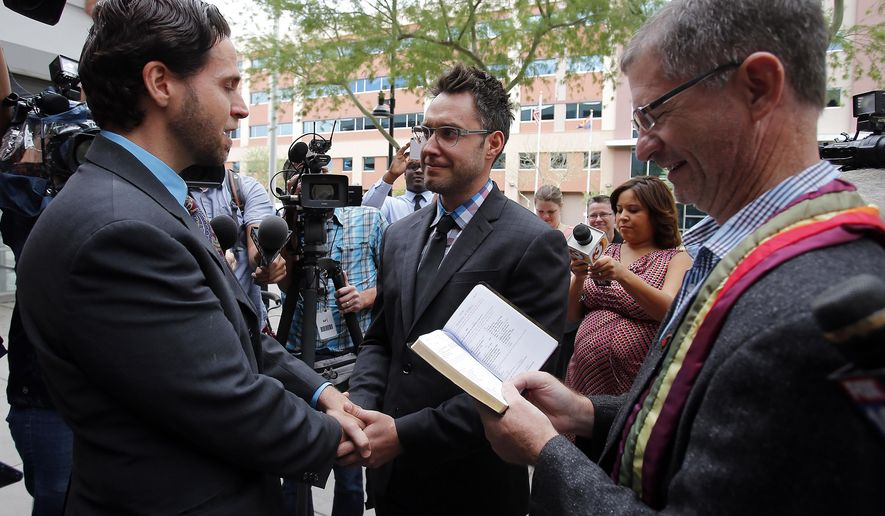Kevin Patterson, left, and David Larance exchange vows as Rev. John Dorhaer, right, officiates the ceremony, Friday, Oct. 17, 2014, in Phoenix. Gay marriage has become legal in Arizona after the state's conservative attorney general said Friday that he wouldn't challenge a federal court decision that cleared the way for same-sex unions in the state. (AP Photo/Rick Scuteri)
