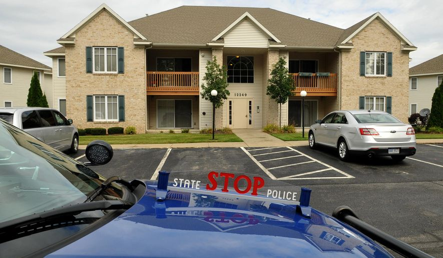 A Michigan State Police car sits parked outside a Crystal Waters condo, where Stacey Grotenhuis' body was found the previous day, in Holland Township, Mich., on Monday, Oct. 6, 2014. The Michigan State Police said they want to examine DNA evidence and computer data regarding the deaths of Grotenhuis and her father, Gary Volkers, before releasing more information. (AP Photo/The Grand Rapids Press, Mlive.com, Mark Copier)