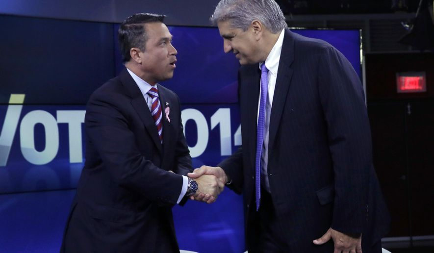 Incumbent Republican Rep. Michael Grimm, left, and Democratic challenger Domenic Recchia shake hands before a recorded, televised debate for the 11th Congressional District race Friday, Oct. 17, 2014, at WABC-TV in New York. (AP Photo/Richard Drew, Pool)