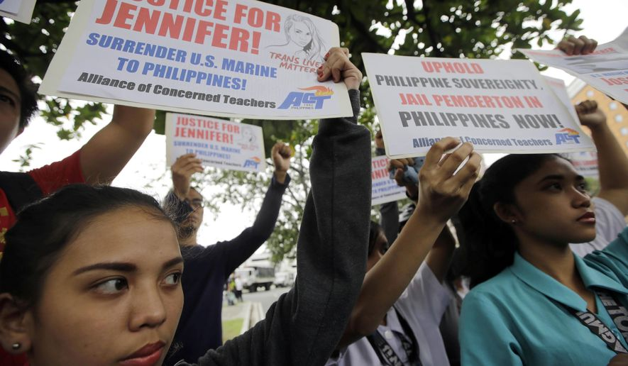 Protesters display placards at a rally at the U.S. Embassy in Manila to reiterate their demand to take custody of a U.S. Marine who is a suspect in the killing of a Filipino transgender Friday, Oct. 17, 2014 in the Philippines.  Police filed a murder complaint two days ago against U.S. Marine Pfc. Joseph Scott Pemberton accused of killing Jennifer Laude, whose former name was Jeffrey. The killing becomes an emotional case and is expected to test the country's military ties with the United States. (AP Photo/Bullit Marquez)