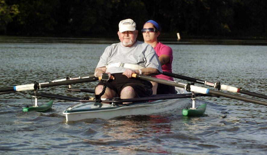 In this Sept. 23, 2014 2014 photo, Hope Creek Care Center's rehabilitation patient, 72-year-old Tom Sisson fulfills a childhood dream by learning to scull a boat as he rows with instructor and Hope Creek physical therapist Nicole Taylor from Aledo in the waters of the Mississippi River near the Sylvan Boathouse in Moline, Ill. (AP Photo/The Dispatch, Gary Krambeck)  QUAD CITY TIMES OUT