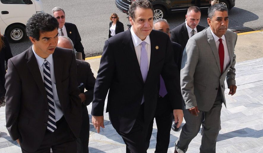 In this photo released by the Dominican Republic presidential office, New York Governor Andrew Cuomo, center, arrives to the presidential palace to meet with President Danilo Medina in Santo Domingo, Dominican Republic, Friday, Oct. 17, 2014.  Cuomo is making campaign visits to Puerto Rico and the Dominican Republic, returning to New York late today. (AP Photo/DR presidential office)
