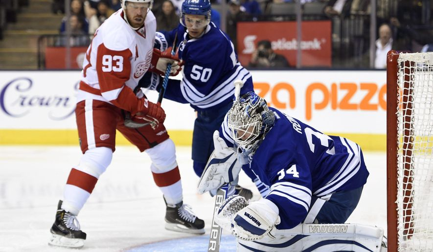 Toronto Maple Leafs goalie James Reimer, right, makes a save as Detroit Red Wings' Johan Franzen (93) and Maple Leafs' Stuart Percy (50) look on during first-period NHL hockey game action in Toronto, Friday, Oct. 17, 2014. (AP Photo/The Canadian Press, Frank Gunn)