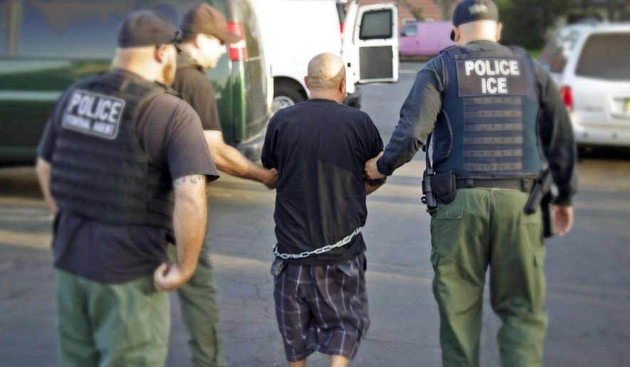 In this Tuesday, Oct. 14, 2014 photo provided by the U.S. Bureau of Immigration and Customs Enforcement (ICE), agents take a person into custody during an immigration sweep in Ontario, Calif. Immigration officials say local authorities across the U.S. released thousands of immigrants from jails this year despite efforts to take them into federal custody, including more than 3,000 with previous felony charges or convictions. They highlight the friction between the federal government and police and sheriff's departments, some of which say holding immigrants beyond their release dates harms community policing efforts. (AP Photo/U.S. Bureau of Immigration and Customs Enforcement)