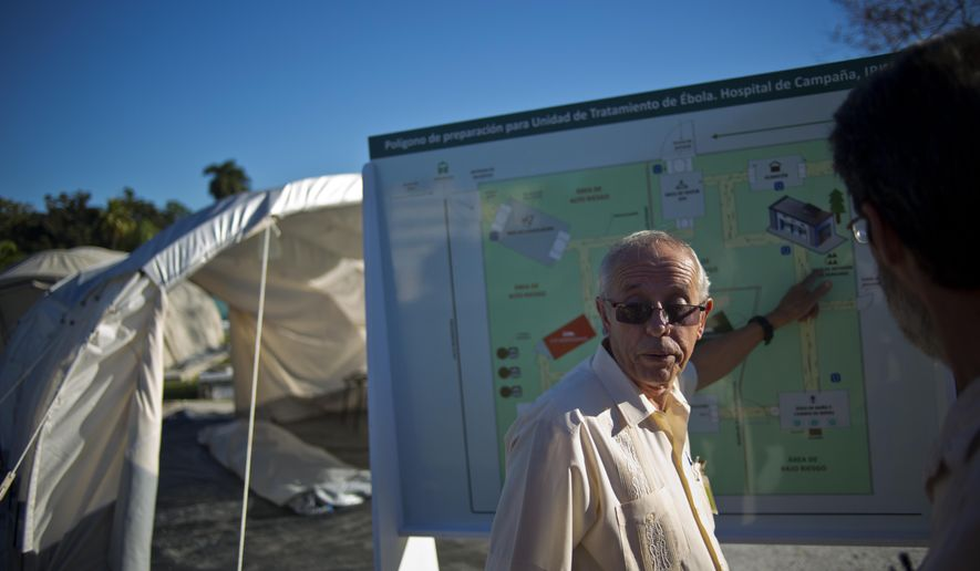 Jorge Perez, the head of Cuba's top tropical medicine institute, points to a map, showing the location of the field hospital set up to train doctors in the fight against Ebola, in Havana, Cuba, Friday, Oct. 17, 2014. Cuba has sent 165 doctors to Sierra Leone and plans to send 296 more to Liberia and Guinea, the largest commitment of medical personnel so far. Perez says Cuba is ready to send more doctors as long as there is enough funding and infrastructure to support them. (AP Photo/Ramon Espinosa)