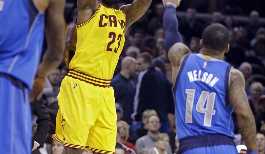 Cleveland Cavaliers' LeBron James (23) shoots over Dallas Mavericks' Jameer Nelson (14) during the first quarter of a preseason NBA basketball game Friday, Oct. 17, 2014, in Cleveland. (AP Photo/Mark Duncan)