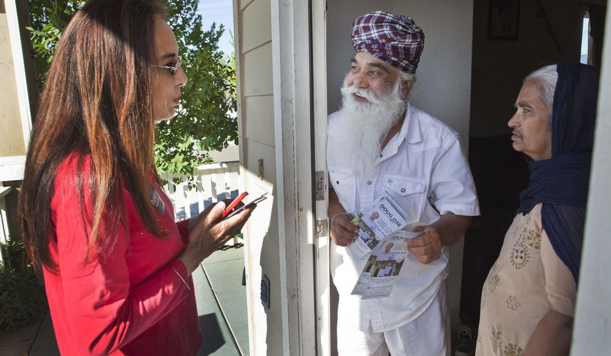 Harmeet Dhillon, left, speaks with Tara Sing Kang, and his wife Rachhpal during a precinct walk to gather support in the Sikh community for Congressional candidate Doug Ose in Elk Grove, Calif., on Saturday, Oct. 11, 2014. Sikh political activists in California are campaigning against freshman Democratic Rep. Ami Bera for what they call his refusal to acknowledge the Indian government's complicity in the massacre of thousands of Sikhs in 1984.(AP Photo/Steve Yeater)