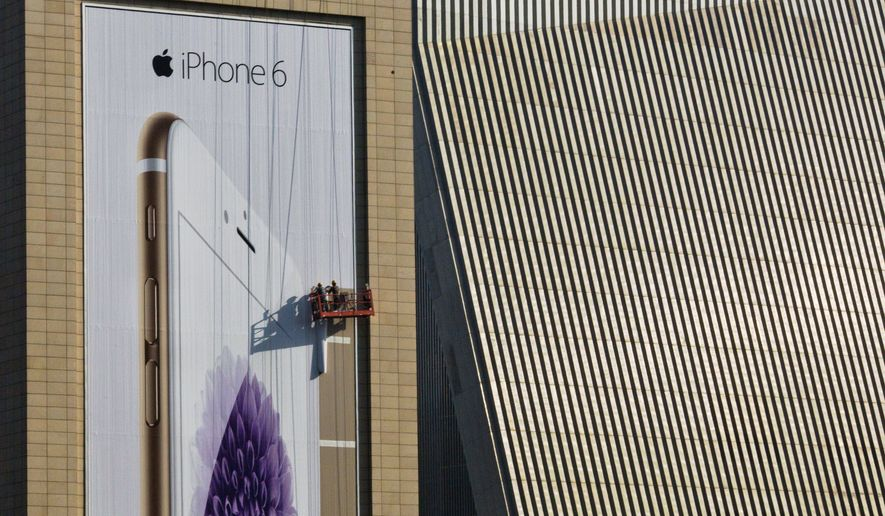 Workers set up a giant advertisement for Apple's iPhone 6 which goes on sale in China, Friday, Oct 17 2014 in Beijing. China is one of Apple's largest and growing market where enthusiasts of the company's latest iPhone are willing to pay thousands of dollars to get their hands on the latest version. (AP Photo/Ng Han Guan)
