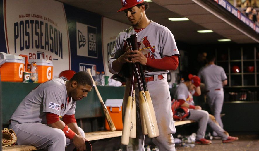 St. Louis Cardinals' Jon Jay leaves the dugout as the San Francisco Giants celebrate on the field after Game 5 of baseball's NL Championship Series, Thursday, Oct. 16, 2014, in San Francisco. The Giants won 6-3, and advanced to the World Series. At left is Oscar Taveras and at right is Tony Cruz. (AP Photo/St. Louis Post-Dispatch, Chris Lee)