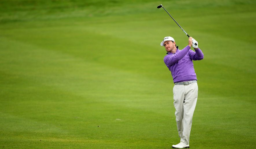 Graeme McDowell plays his shot from the fairway on the 13th hole during day three of the World Match Play Championship at The London Golf Club in Ash, England, Friday Oct. 17, 2014. (AP Photo/PA, John Walton) UNITED KINGDOM OUT  NO SALES  NO ARCHIVE