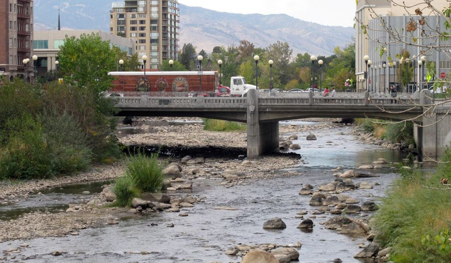 Traffic crosses the Center Street bridge in downtown Reno, Nev., on Friday, Oct. 17, 2014, over the Truckee River, which has been reduced to a shallow stream. Lake Tahoe dropped below its natural rim level for the first time in five years this week, which cut off flows into the river as it meanders 30 miles down the Sierra and through Reno on a 90-mile journey to Pyramid Lake. (AP Photo/Scott Sonner)