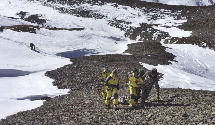 In this photo provided by the Nepalese Army, rescue team members carry a victim of an avalanche before they airlift the body from Thorong La pass area in Nepal, Thursday, Oct. 16, 2014. Search teams in army helicopters rescued dozens of stranded foreign trekkers and recovered more bodies of victims of a blizzard and avalanches in the mountains of northern Nepal on Thursday. (AP Photo/The Nepalese Army)