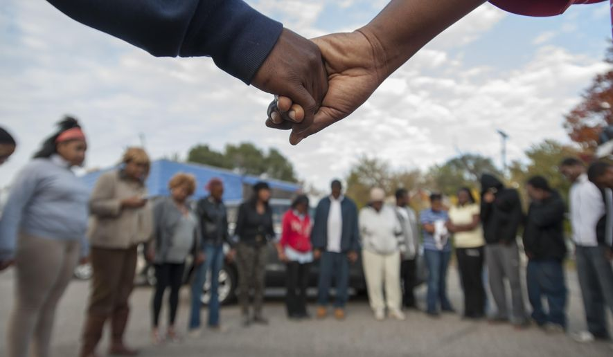 In this photo taken on Thursday, Oct. 16, 2014, a group of onlookers form a prayer circle for the victims of a shooting at a home in Detroit, where a young child was killed and three others were injured. Detroit Police Chief James Craig says a young man and woman have been arrested, but investigators believe there are four more suspects. (AP Photo/Detroit News, David Guralnick)  DETROIT FREE PRESS OUT, HUFFINGTON POST OUT, MAGS OUT, MANDATORY CREDIT