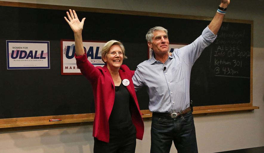 U.S. Sens. Elizabeth Warren, left, D-Mass., and Mark Udall, D-Colo., wave to a gathered crowd during a rally to urge the reelection of Udall to the Senate, on the campus of the University of Colorado, in Boulder, Colo., Friday, Oct. 17, 2014. (AP Photo/Brennan Linsley)