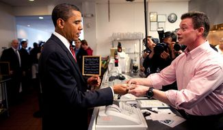 President Barack Obama gets his change after paying for his lunch as he and Vice President Joe Biden make an unannounced visit to Ray's Hell Burger in Arlington, Va., May 5, 2009. White House photo.