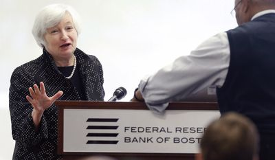 Federal Reserve Chairman Janet Yellen, left, reacts as a technician works to resolve a computer problem during her speech at a conference on economic opportunity at the Federal Reserve Bank in Boston, Friday, Oct. 17, 2014. (AP Photo/Michael Dwyer)